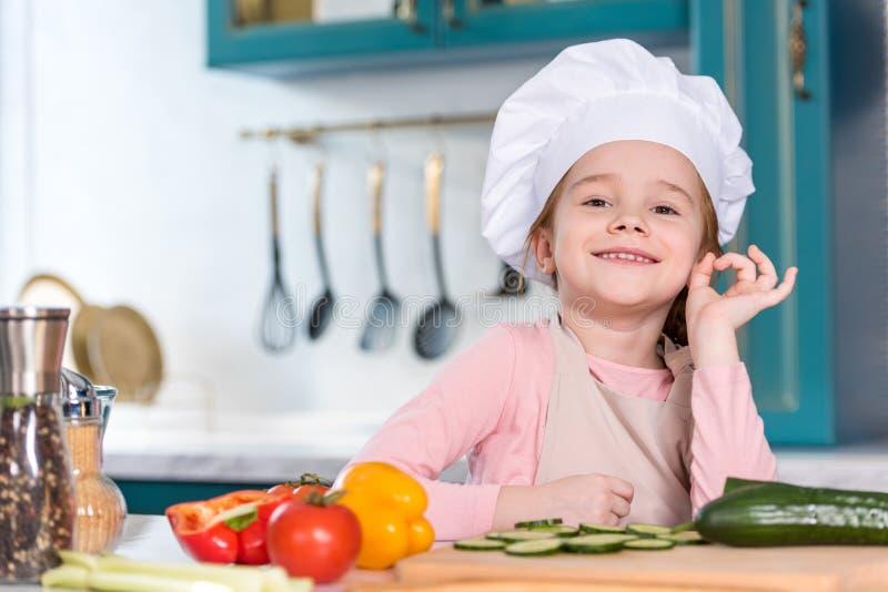 прелестный ребенок в шляпе шеф-повара показывая одобренный знак и усмехаясь на камере стоковое изображение