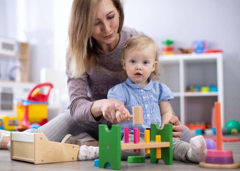 Прелестный ребенок играя с воспитательными игрушками в питомнике Счастливый здоровый ребенок имея потеху с красочными различными  стоковое фото