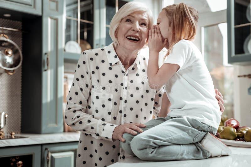 Прелестный ребенок сидя на секретах таблицы и шептать к бабушке стоковое изображение rf