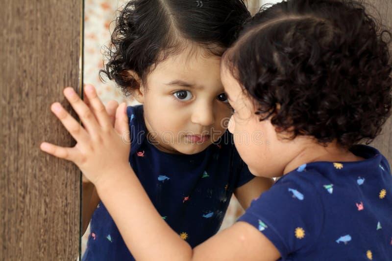 Прелестный ребенок смотря животики его отражение в зеркале стоковая фотография