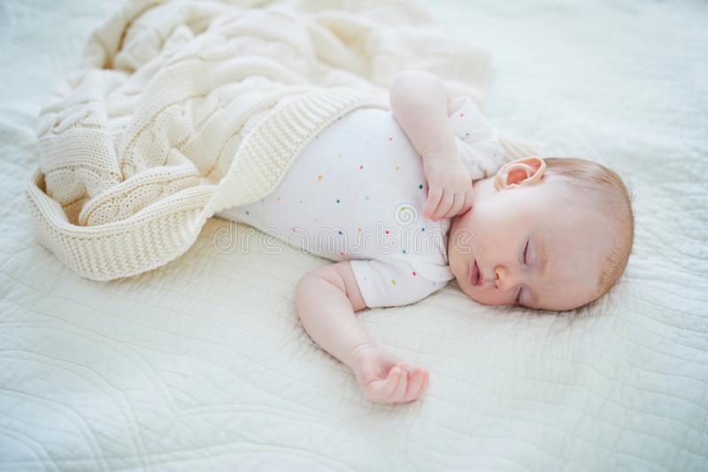 Прелестный ребенок спать в шпаргалке под связанным одеялом стоковые изображения rf
