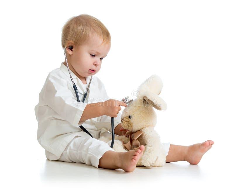 Прелестный ребенок с одеждами доктора и зайцы toy стоковые изображения