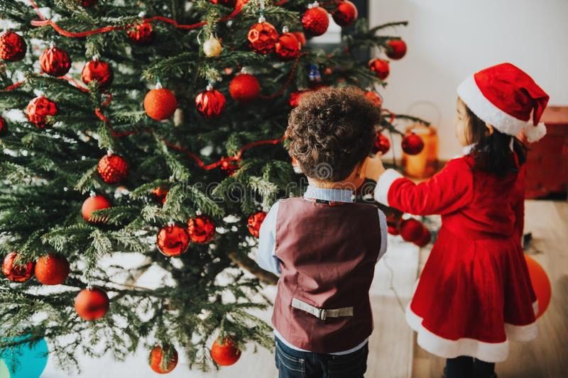 2 прелестных 3-ти летних дет играя рождественской елкой стоковое фото