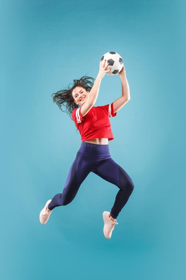 Препровождайте к победе Молодая женщина как футболист футбола скача и пиная шарик на студии на пинке стоковое фото rf