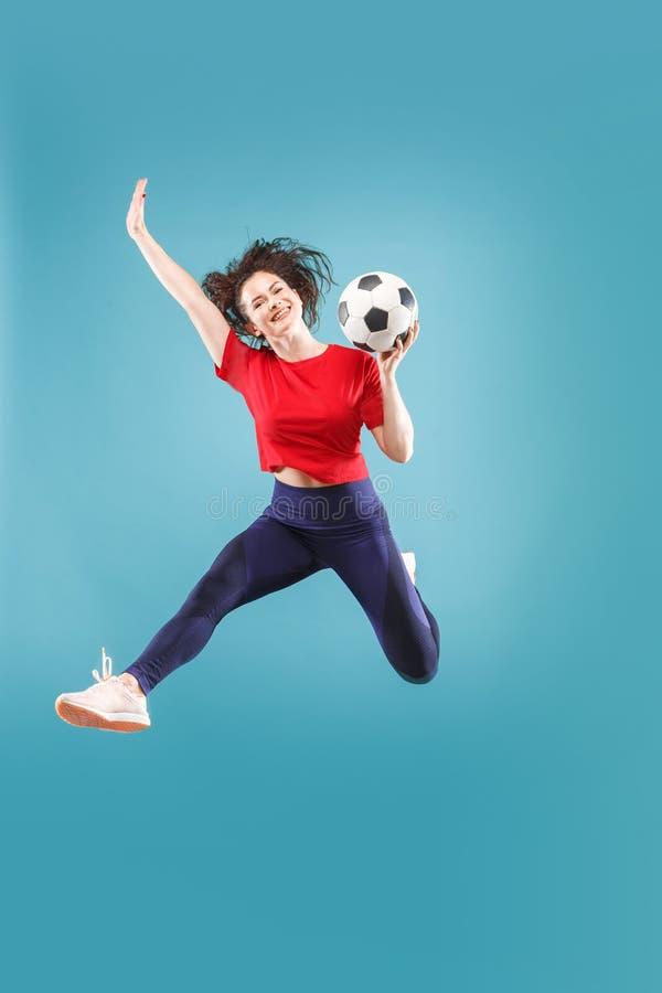 Препровождайте к победе Молодая женщина как футболист футбола скача и пиная шарик на студии на пинке стоковая фотография