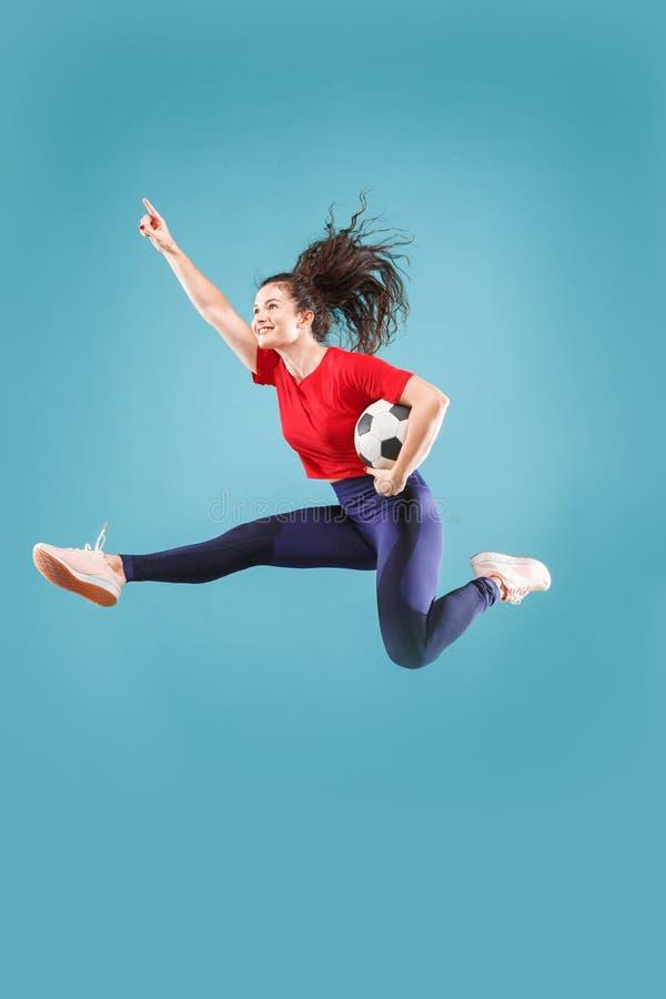 Препровождайте к победе Молодая женщина как футболист футбола скача и пиная шарик на студии на пинке стоковые изображения