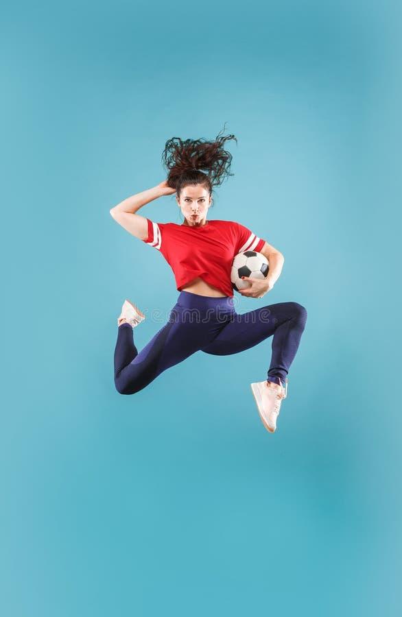 Препровождайте к победе Молодая женщина как футболист футбола скача и пиная шарик на студии на пинке стоковые изображения rf