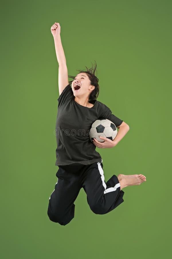Препровождайте к победе Молодая женщина как футболист футбола скача и пиная шарик на студии на зеленом цвете стоковое изображение rf