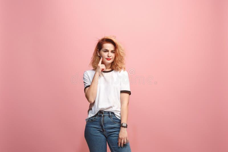 препятствуйте мне думать Сомнительная задумчивая женщина при заботливое выражение делая выбор против розовой предпосылки стоковые фотографии rf