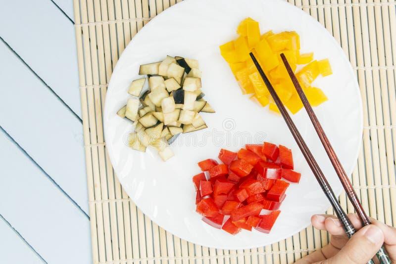 Прерванные болгарские перцы и баклажан на белой плите Руки женщины держа ручки еды Взгляд сверху на деревянном столе скопируйте к стоковые фотографии rf