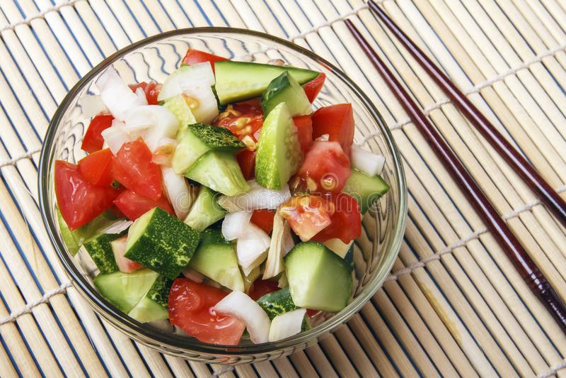 Прерванные овощи - огурцы, томаты и луки в стеклянном шаре и палочке на бамбуковой циновке над взглядом скопируйте космос стоковая фотография rf