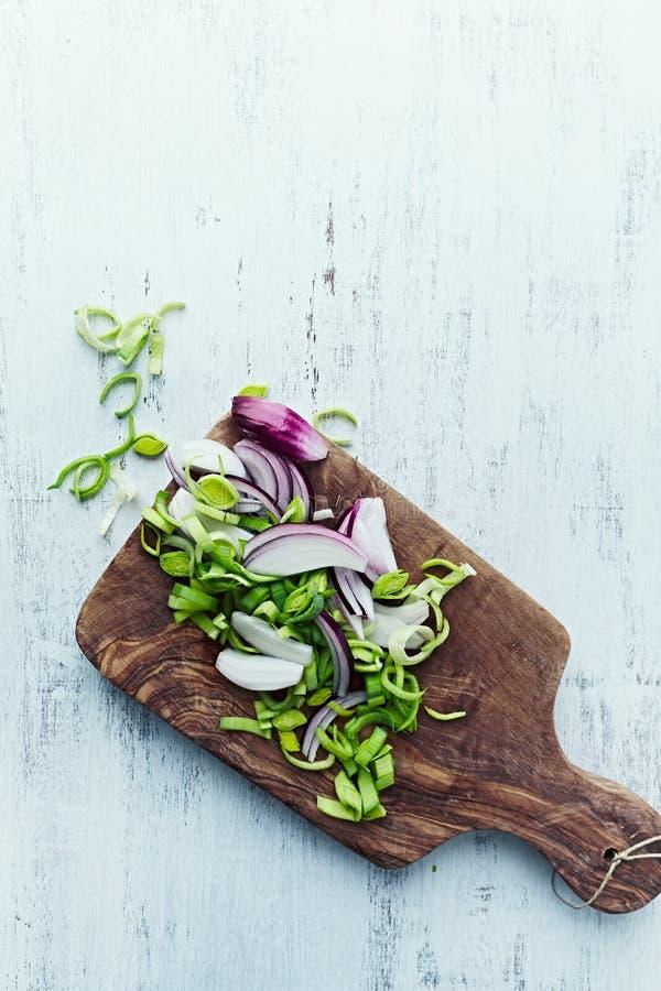 Прерванные лук-порей и лук на деревянной доске кухни стоковое изображение rf