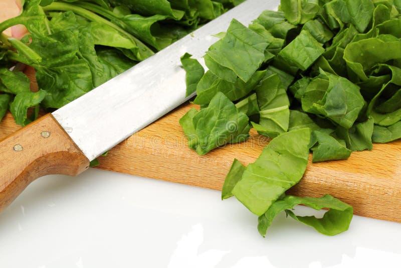 Прерванные шпинат и нож на деревянной доске стоковые фотографии rf