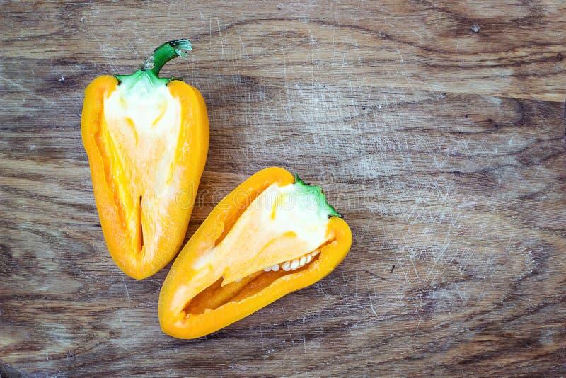 Прерванный перец отрезка красочный живой яркий желтый свежий зрелый сладостный на старой предпосылке таблицы деревянной доски выр стоковые фото
