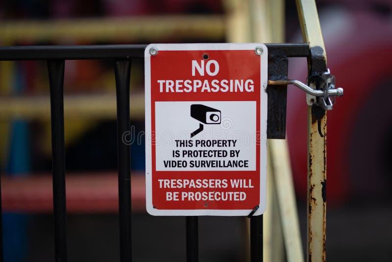 Преследовать в судебном порядке в судебном порядке предупредительный знак не отправляет SMS никакому Trespassing видео- наблюдени стоковое фото