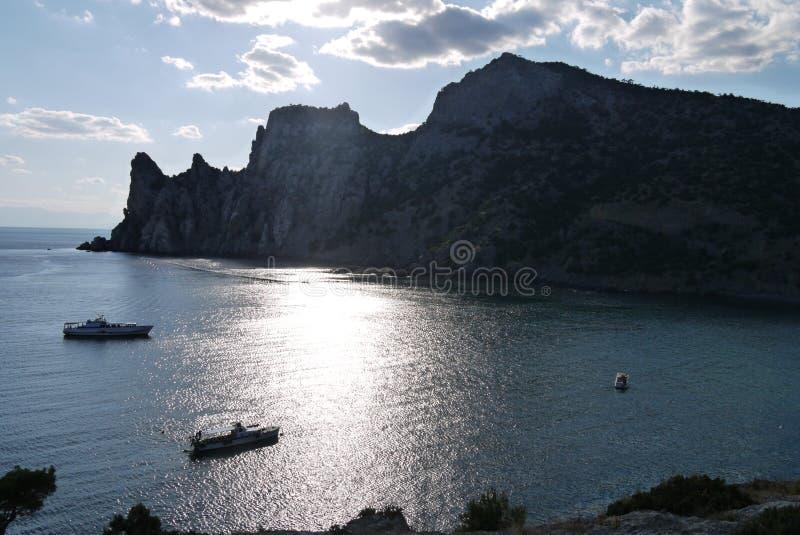Преследуйте в Чёрном море на предпосылке крутых скал покрытых с травой Идти на шлюпку стоковое изображение