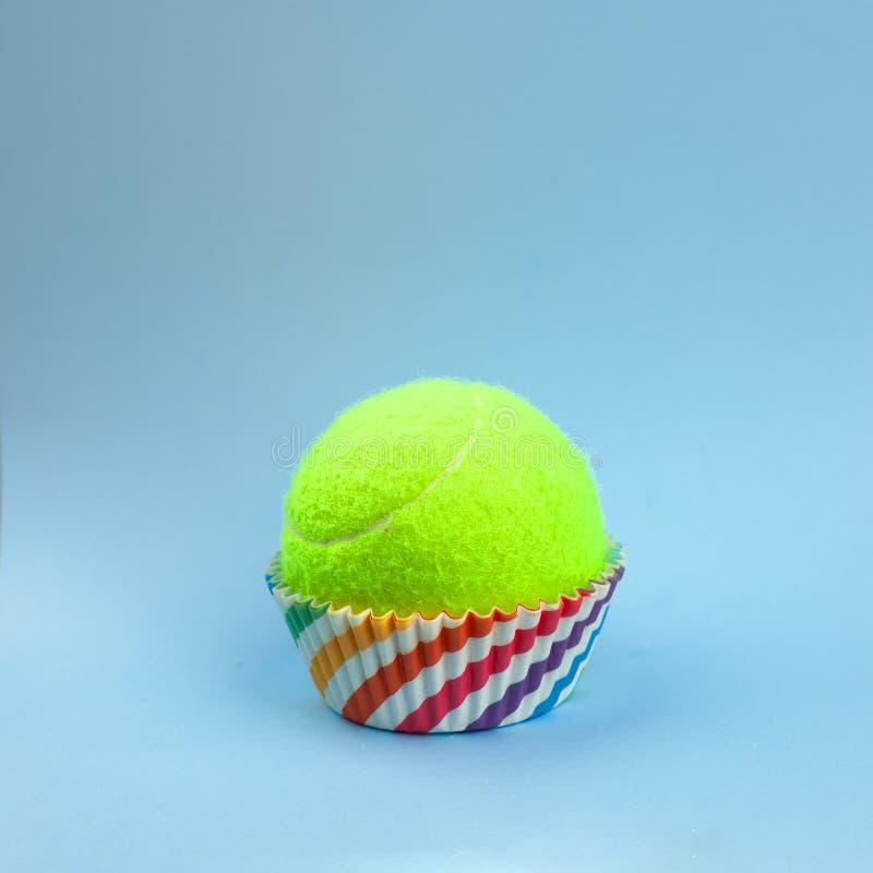 Прессформа радуги для пирожного и теннисный мяч на голубой предпосылке, минимальном творческом спорте или идее печенья Плоское по стоковые изображения