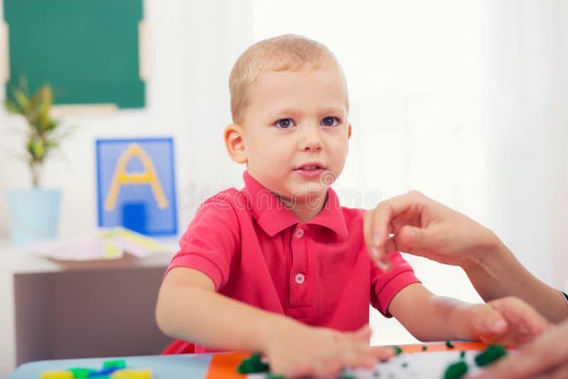 Прессформы мальчика от пластилина на таблице стоковое фото rf