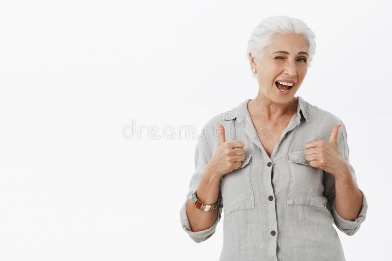 Престарелый утес консервной банки тоже Портрет очаровательной восторженной бабушки с серыми волосами в свободной рубашке показыва стоковое изображение