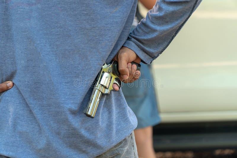 Преступники держат оружие за женщиной которая около раскрыть автомобильную дверь Концепция социальных бедствий вопроса и преступл стоковое изображение rf