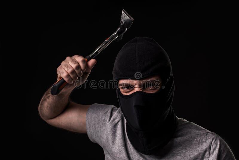 Преступник в футболке и балаклаве с молотком стоковые фотографии rf