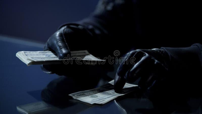 Преступник в черных перчатках подсчитывая пачку денег заработанную для совершая злодеяния стоковая фотография