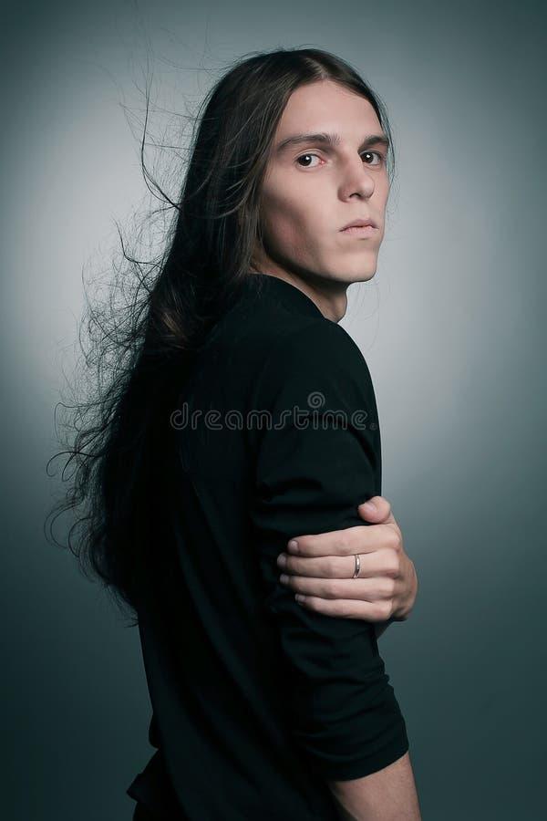 Претендующий на тонкий вкус портрет модной мужской модели с длинными волосами стоковое изображение rf