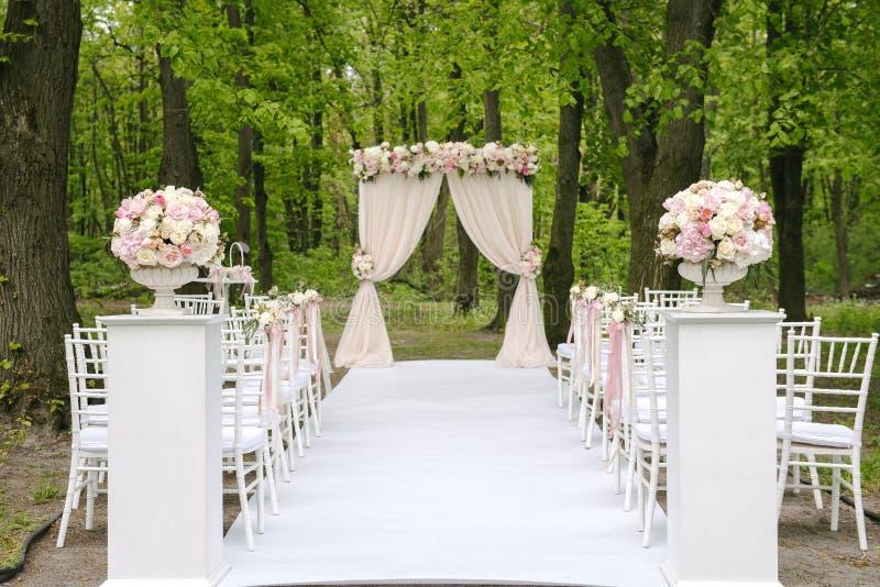 Прелестная арка свадьбы с выровнянный вверх по стульям стоковые фотографии rf