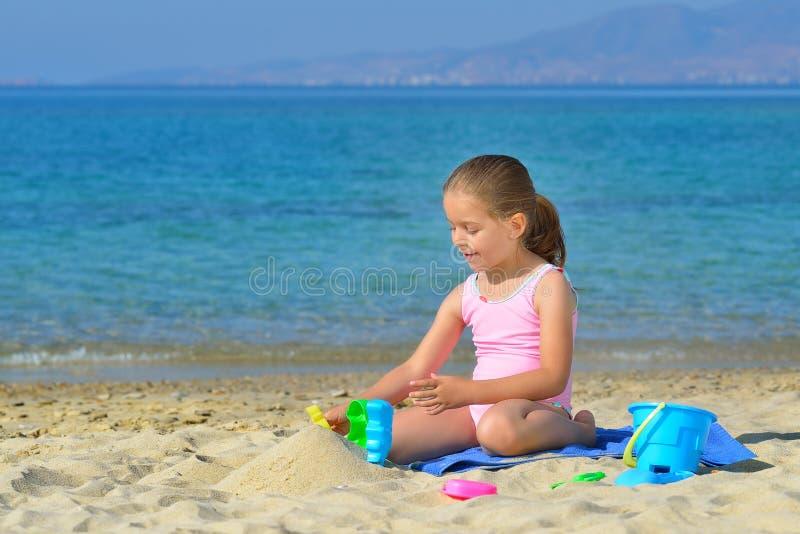 Прелестная девушка малыша играя с ее игрушками на пляже стоковые фотографии rf