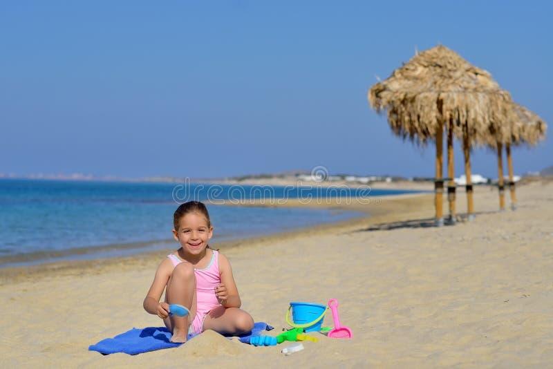 Прелестная девушка малыша играя с ее игрушками на пляже стоковая фотография rf