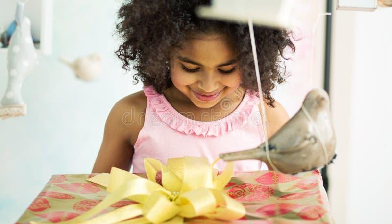 Прелестная девушка раскрывая подарок на день рождения стоковое фото rf
