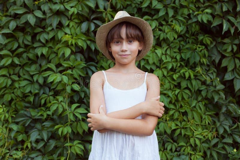Прелестная девушка стоя на предпосылке листва стоковая фотография rf