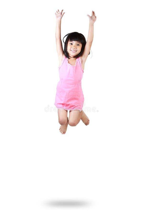 Прелестная и счастливая маленькая азиатская девушка скача в воздух стоковое изображение rf