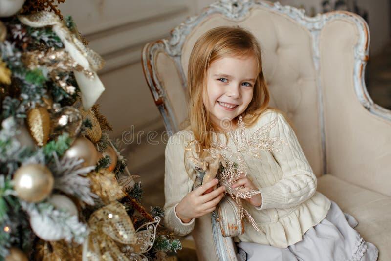 Прелестная маленькая белокурая девушка с голубыми глазами усмехаясь в interio стоковые фотографии rf