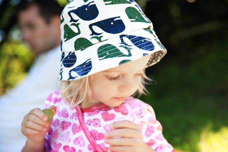 Прелестная маленькая девочка в держать зеленую виноградину в руке стоковые изображения