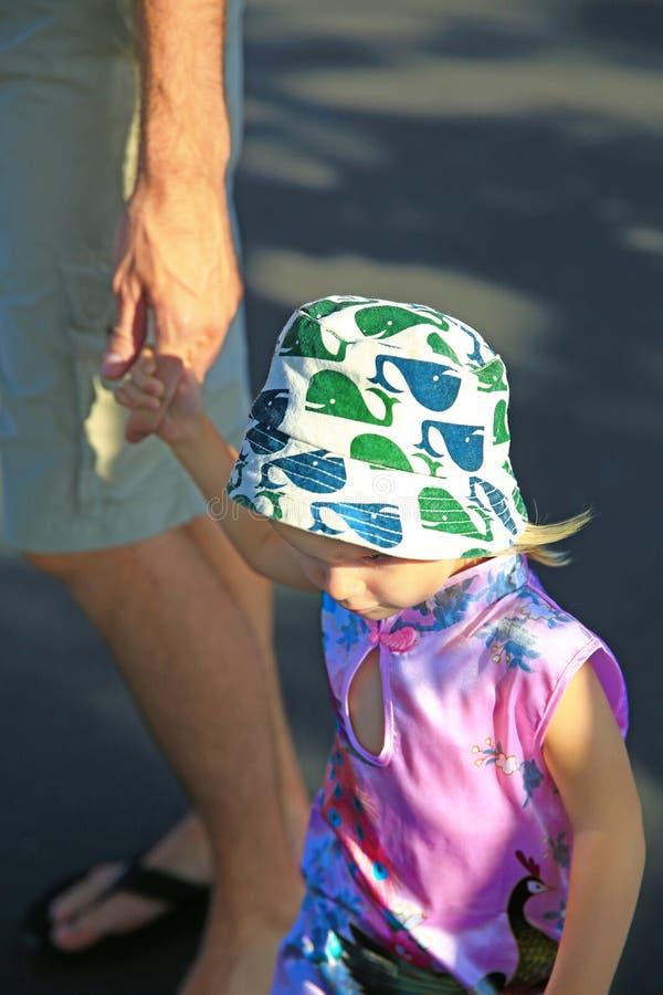Прелестная маленькая девочка держа ее руку отца стоковое изображение rf