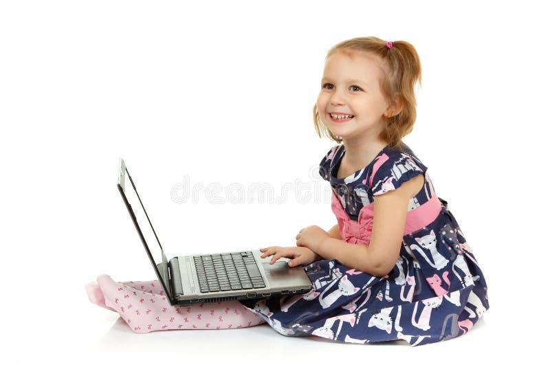 Прелестная маленькая девочка используя компьтер-книжку стоковое фото