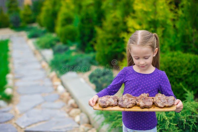 Download Прелестная маленькая девочка с зажаренными стейками в руках внешних Стоковое Фото - изображение насчитывающей прелестное, пожар: 40587108