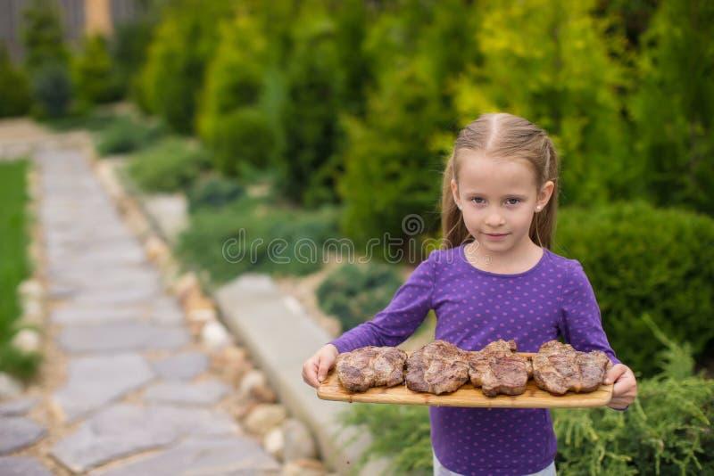 Download Прелестная маленькая девочка с зажаренными стейками в руках внешних Стоковое Изображение - изображение насчитывающей жечь, ребенок: 40587171