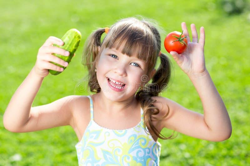 Прелестная маленькая девочка с овощами внешними стоковая фотография