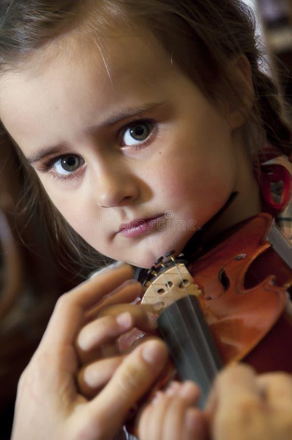 Прелестная маленькая девочка уча играть скрипки стоковое фото rf