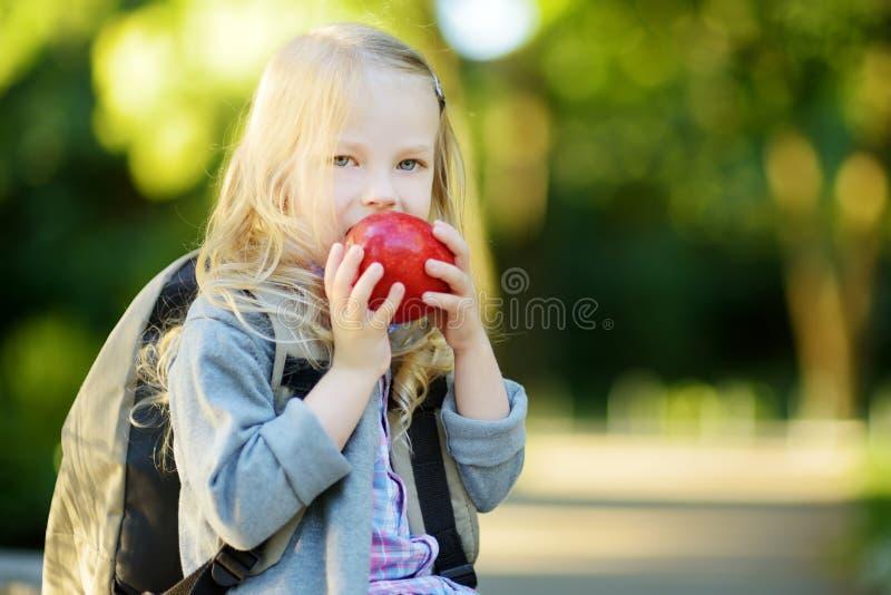 Прелестная маленькая школьница изучая outdoors на яркий день осени Молодой студент делая ее домашнюю работу Образование для малых стоковая фотография