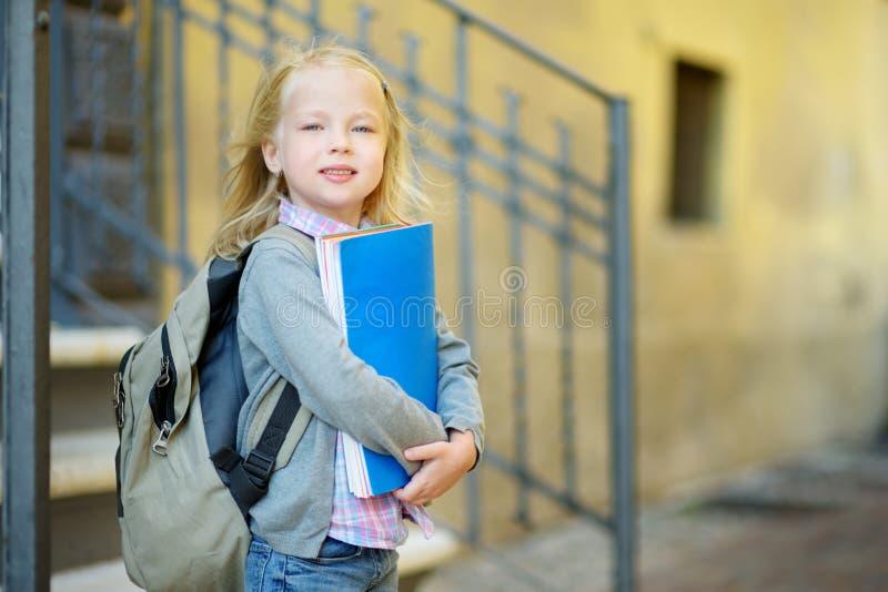 Прелестная маленькая школьница изучая outdoors на яркий день осени Молодой студент делая ее домашнюю работу Образование для малых стоковые фотографии rf
