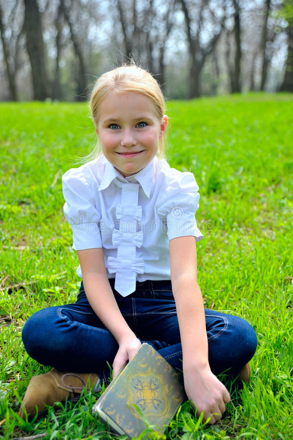 Прелестная милая маленькая девочка с книгой снаружи дальше стоковые изображения rf