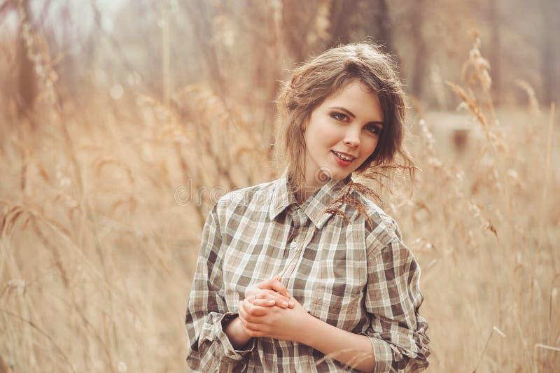 Прелестная молодая женщина в рубашке шотландки на уютной прогулке страны на поле стоковые изображения