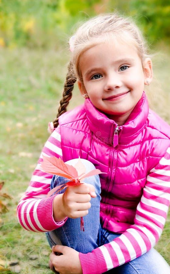 Прелестная усмехаясь маленькая девочка сидя на траве стоковая фотография