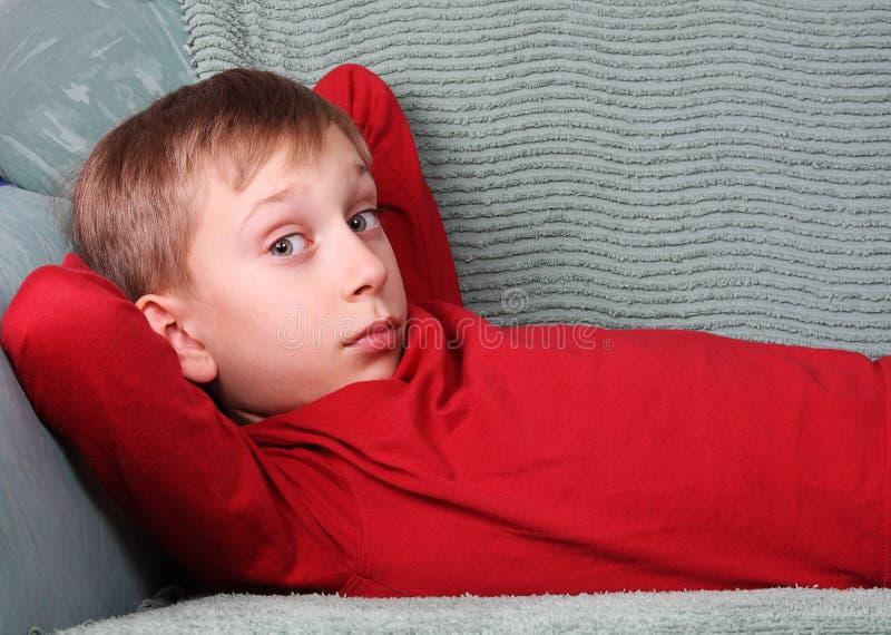 Белокурый кавказский мальчик в красный лежать на зеленой софе смотря в удивленную камеру стоковые фотографии rf