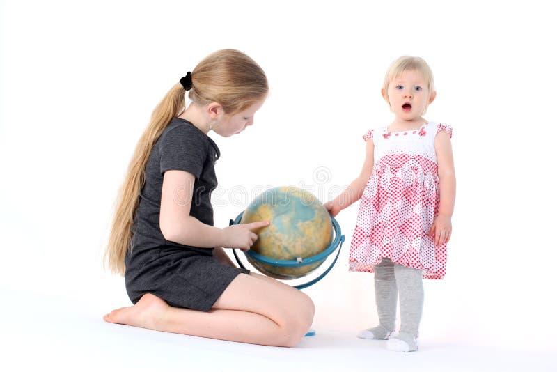 прелестные маленькие 2 сестры с глобусом стоковое фото rf