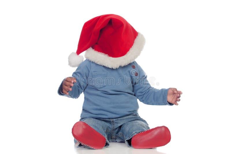 Прелестный африканский младенец при шляпа рождества покрывая его сторону стоковое изображение