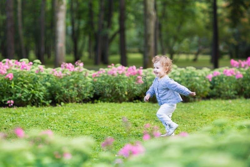 Прелестный курчавый ребёнок бежать в красивом парке стоковые фотографии rf